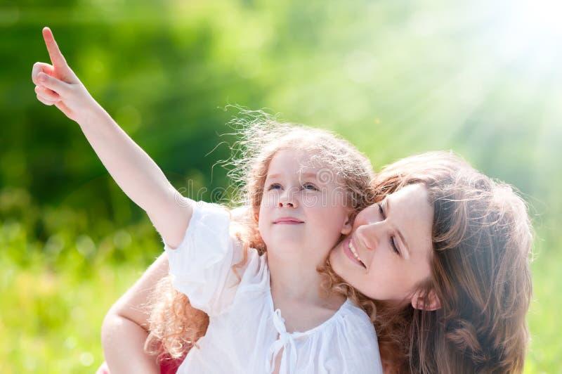 Mooi meisje dat aan haar moeder toont stock afbeelding