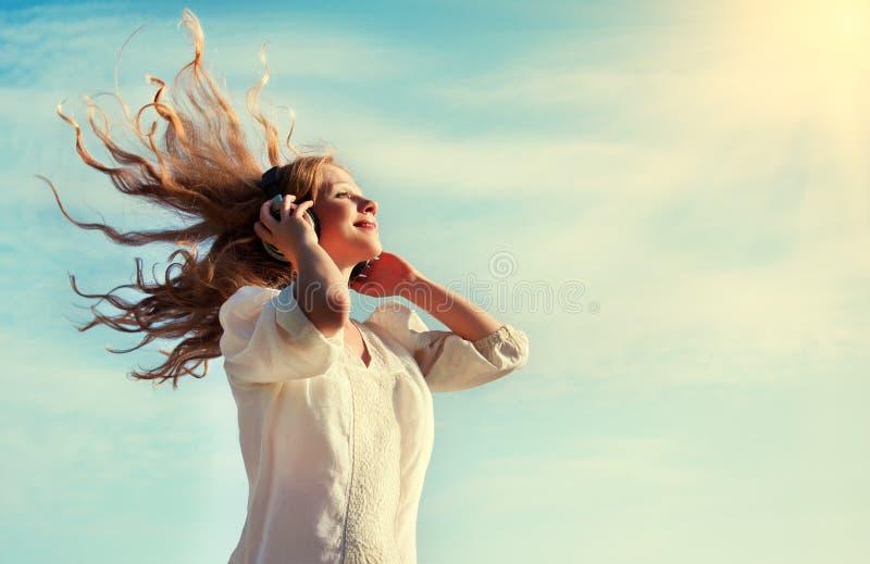 Mooi meisje dat aan muziek op hoofdtelefoons luistert stock foto's