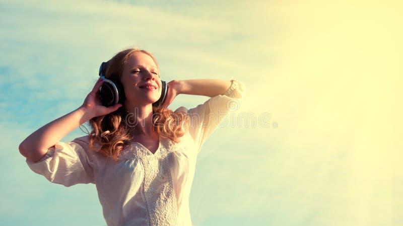 Mooi meisje dat aan muziek op hoofdtelefoons luistert royalty-vrije stock foto's