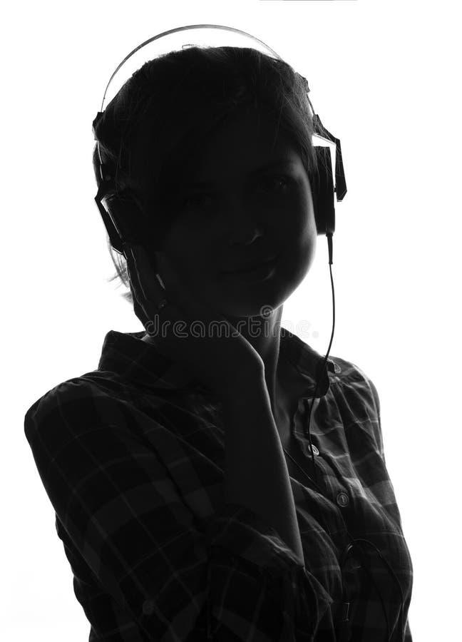 Mooi meisje dat aan muziek op hoofdtelefoons luistert stock afbeelding