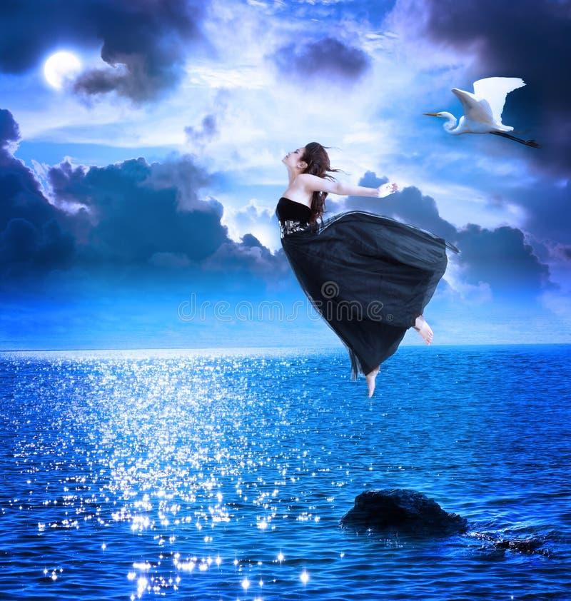 Mooi meisje dat in de blauwe nachthemel springt royalty-vrije stock fotografie