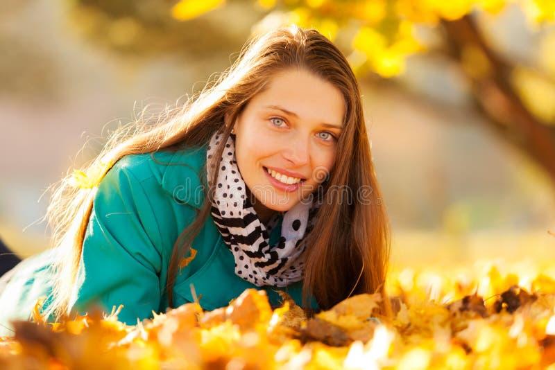 Mooi meisje dat in de herfstbladeren ligt stock afbeelding
