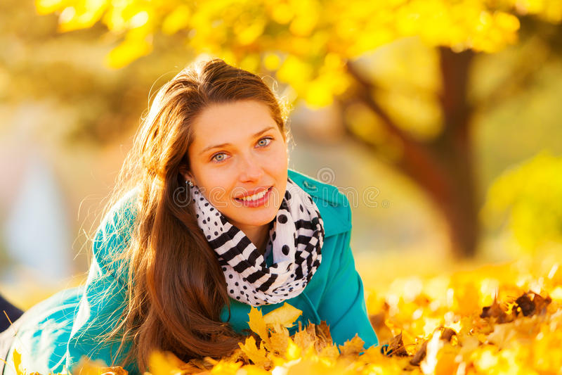 Mooi meisje dat in de herfstbladeren ligt royalty-vrije stock fotografie