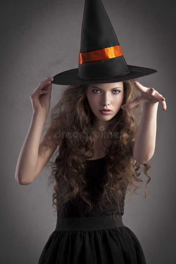 Mooi meisje dat een reusachtige heksenhoed draagt stock foto