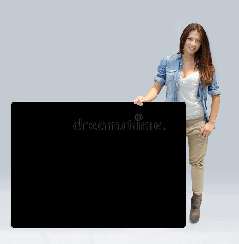 Mooi meisje dat grote zwarte raad houdt stock foto's