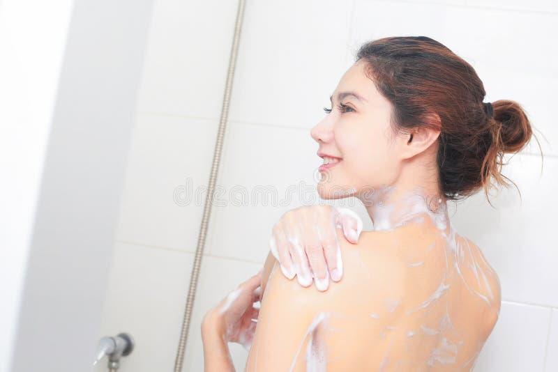 Mooi meisje dat haar gel van de lichaamsdouche in badkamers wast stock afbeelding
