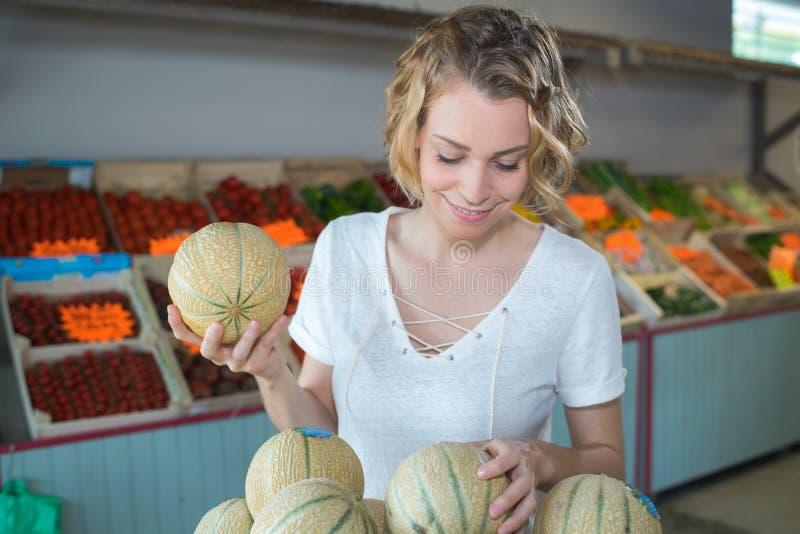 Mooi meisje dat in kruidenierswinkelopslag smakelijke meloen kiest royalty-vrije stock fotografie