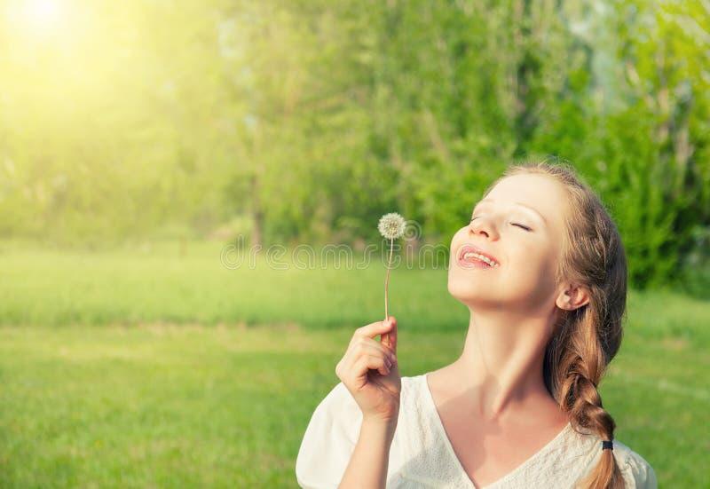 Mooi meisje dat met paardebloem van zon geniet stock afbeelding