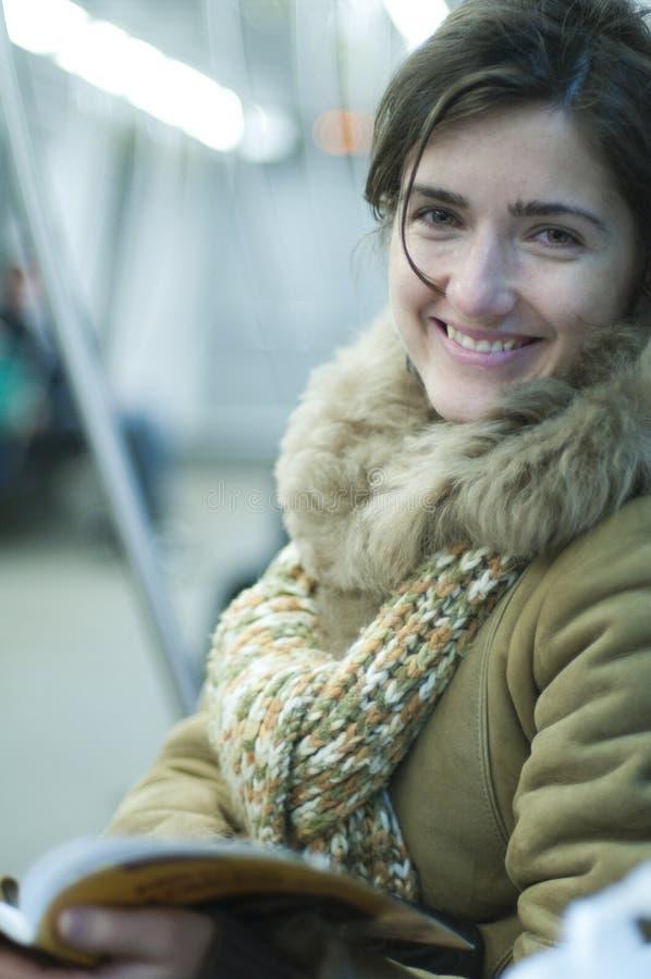 Mooi meisje dat in metro glimlacht stock foto's