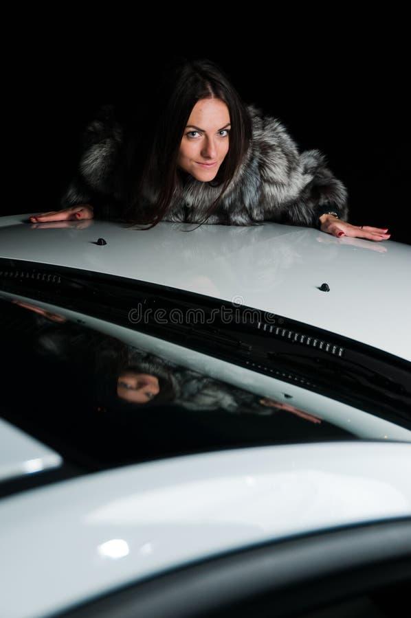 Mooi meisje dat op autokap legt royalty-vrije stock fotografie