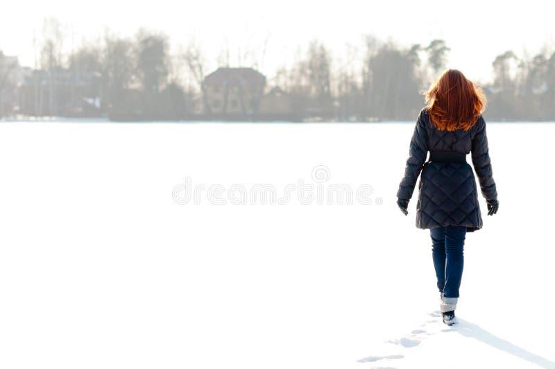 Mooi meisje dat op bevroren meer loopt stock afbeelding
