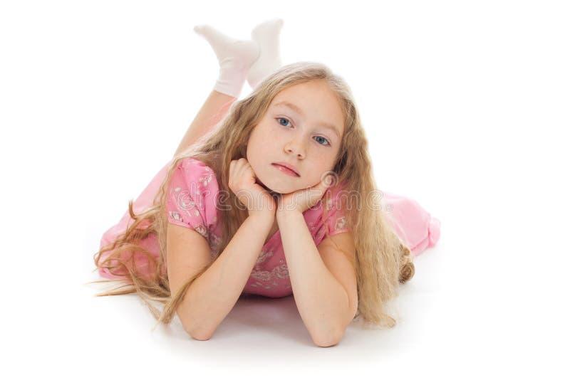 Mooi meisje dat op geïsoleerdek vloer in studio ligt stock afbeelding
