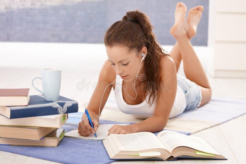 Mooi meisje dat thuis het leggen op vloer leert stock fotografie