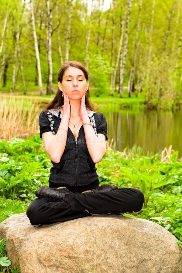 Mooi meisje dat yoga op de rots doet dichtbij het meer royalty-vrije stock afbeelding