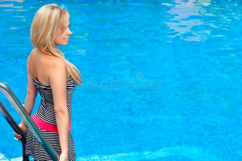 Mooi meisje dat zich door de pool bevindt stock afbeelding
