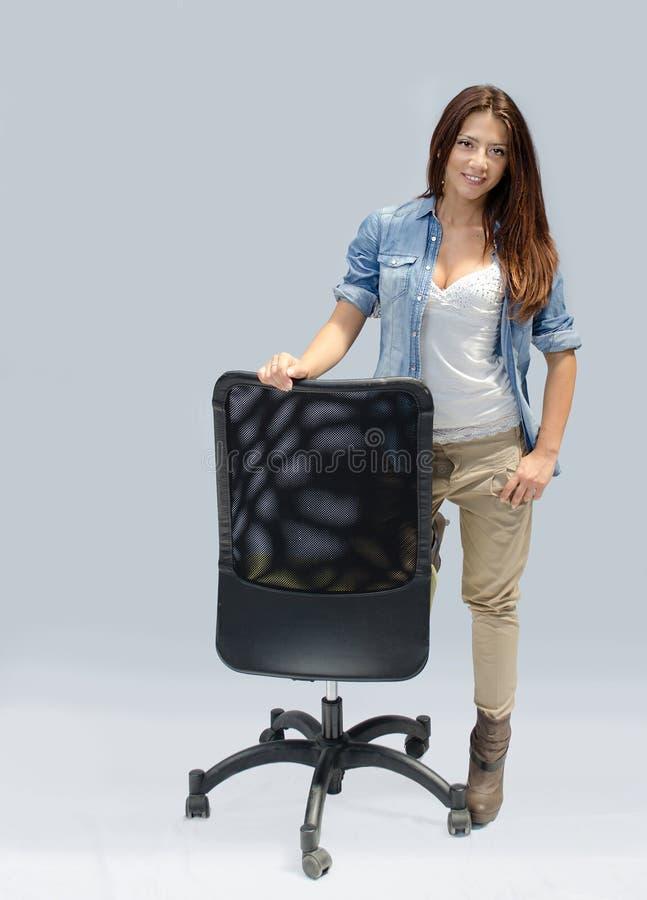 Mooi meisje dat zich naast een bureaustoel bevindt stock afbeelding