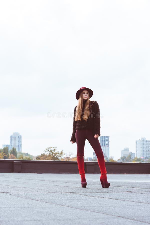 Mooi meisje in de hoed van Bourgondië en de herfstuitrusting het stellen op a stock foto