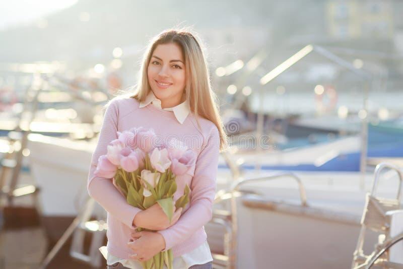 Mooi meisje in de lente of de herfst, door het overzees in de bootbaai Met een boeket van bloemen in zijn handen en strakke modie royalty-vrije stock foto's