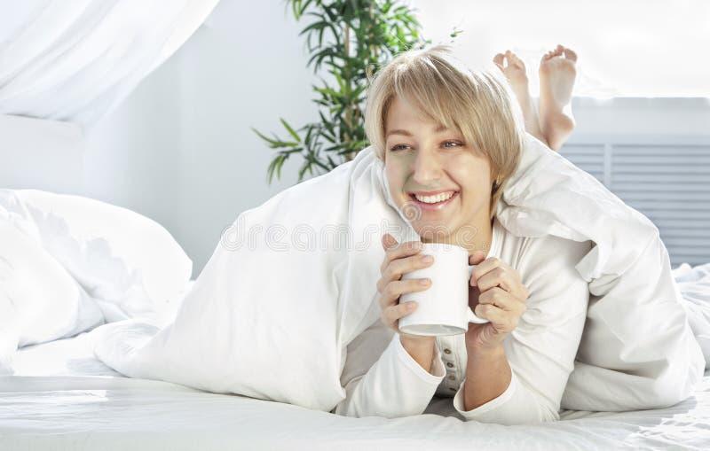 Mooi meisje in de ochtend in bed met kop royalty-vrije stock foto's