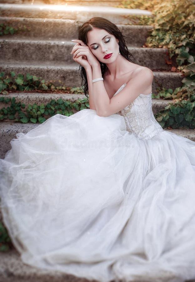 Mooi meisje in de weelderige kleding in de tuin Aantrekkelijke donkerbruine vrouw in een lange witte kleding, die in een struik b royalty-vrije stock afbeeldingen