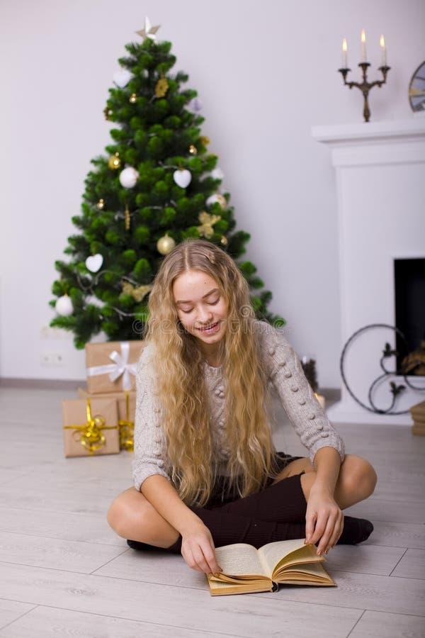 Mooi meisje dichtbij een Kerstboom in de ruimte royalty-vrije stock fotografie