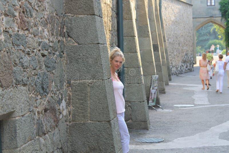 Mooi meisje dichtbij een steenmuur stock foto