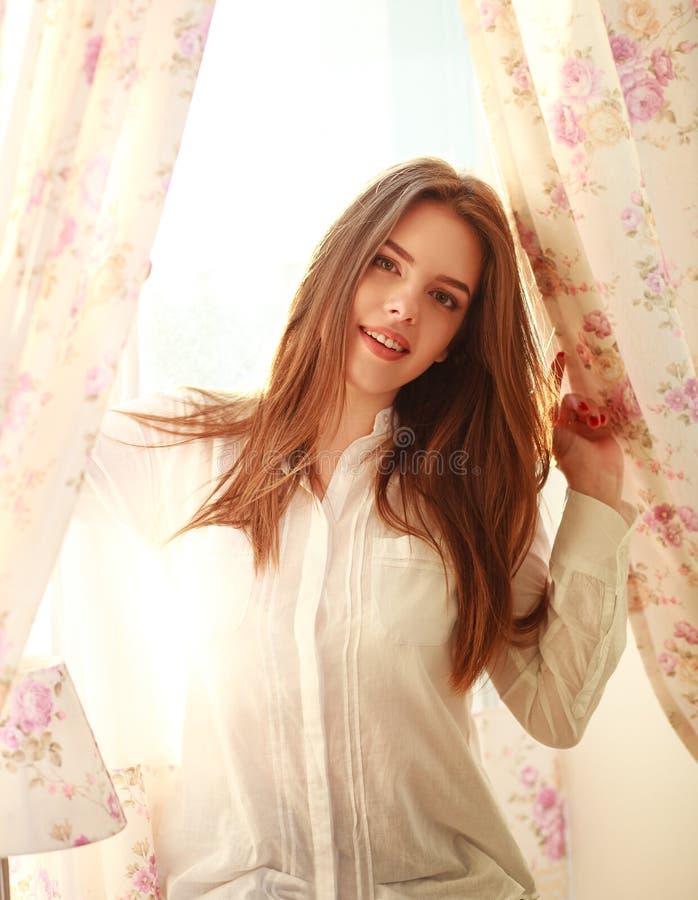 Mooi meisje dichtbij het venster in ochtendzonlicht royalty-vrije stock foto's