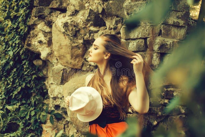 mooi meisje dichtbij steenachtige muur royalty-vrije stock foto