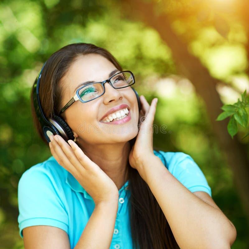 Mooi meisje die aan de muziek luisteren die hoofdtelefoons dragen royalty-vrije stock foto