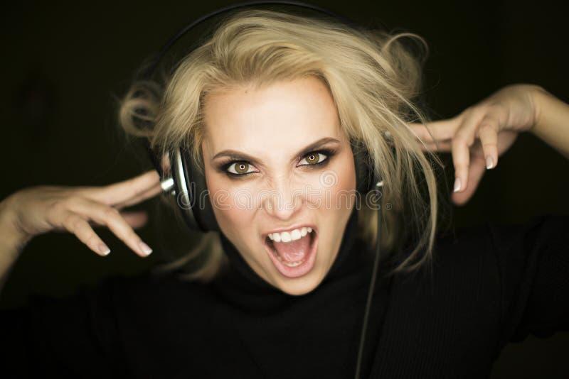 Mooi meisje die aan muziek tegen donkere achtergrond luisteren stock fotografie