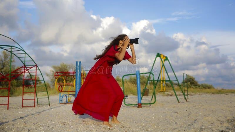Mooi meisje die beeld op het overzeese strand in rode kleding nemen royalty-vrije stock fotografie