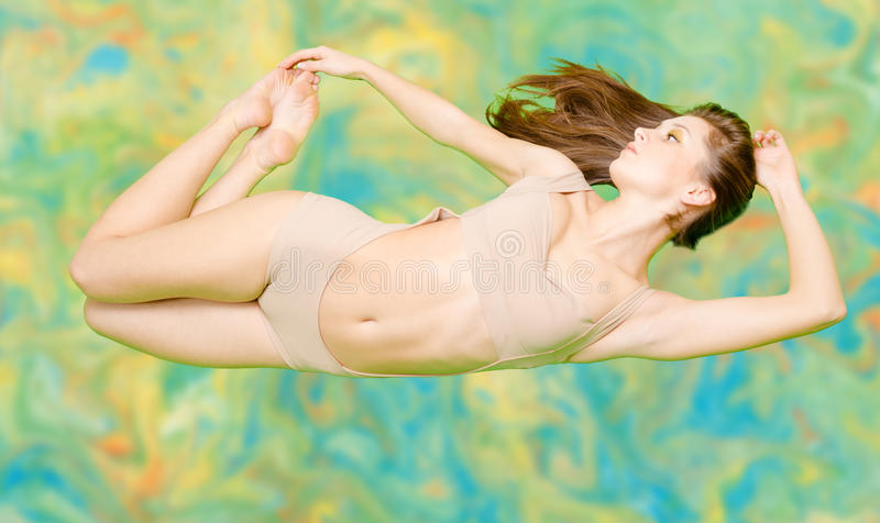 Mooi meisje die in beige zwempak op samenvatting drijven stock afbeeldingen