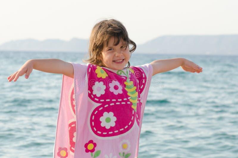Mooi meisje die bij kust in roze vlinderhanddoek glimlachen royalty-vrije stock afbeeldingen