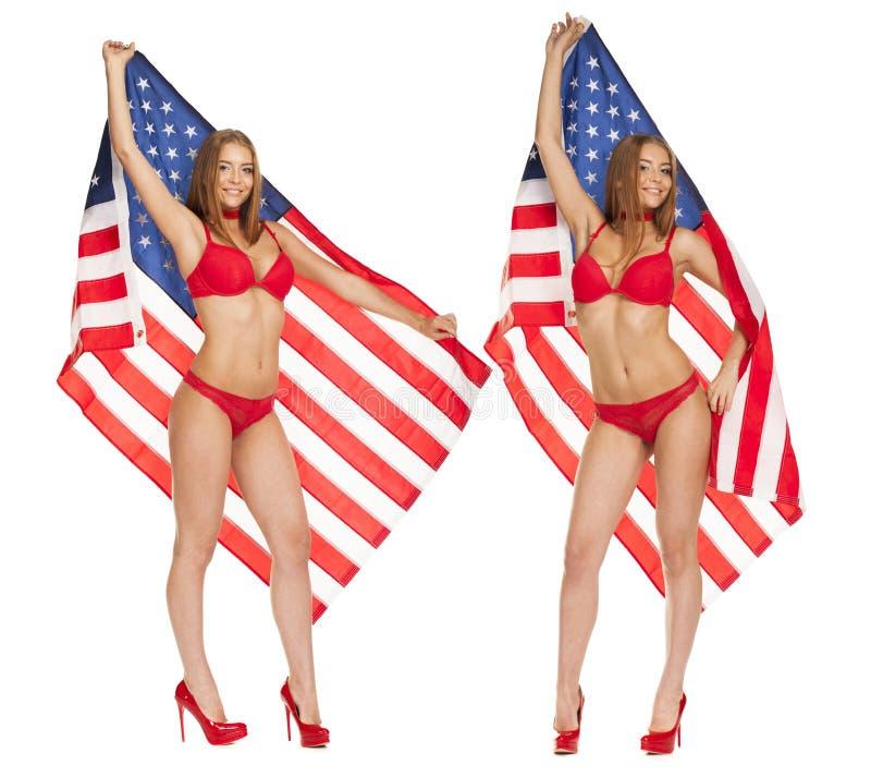 Mooi meisje die in bikini de vlag van de V.S. houden stock foto