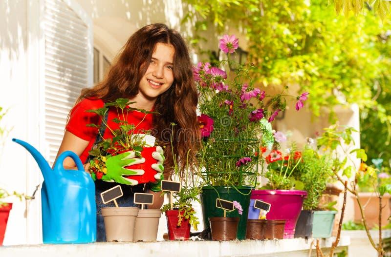 Mooi meisje die bloemen in potten op balkon planten royalty-vrije stock afbeeldingen