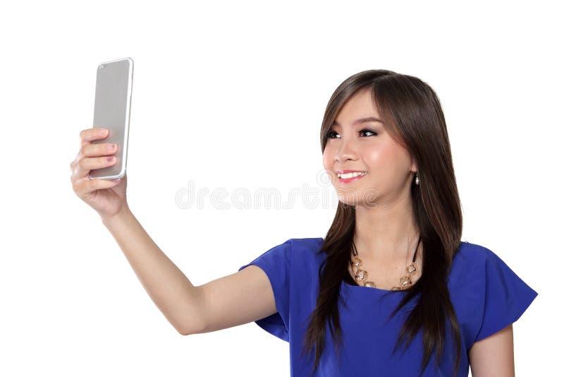 Mooi meisje die die celtelefoon voor videogesprek met behulp van, op wit wordt geïsoleerd stock afbeeldingen