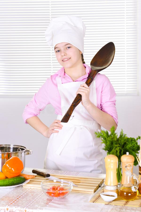 Mooi meisje die chef-kok eenvormig met grote lepel op keuken dragen royalty-vrije stock afbeeldingen