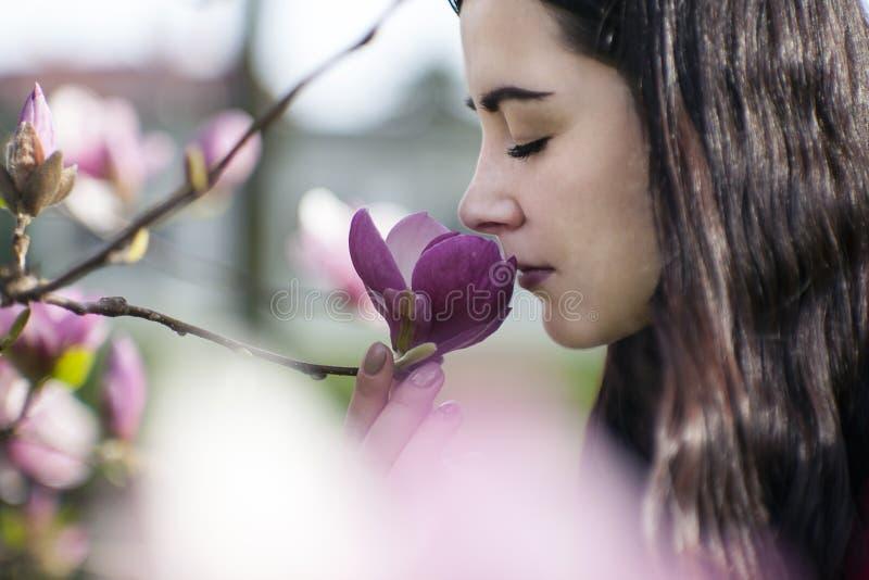 Mooi meisje die de bloemen ruiken Tot bloei komende magnolia in de parktuin stock afbeelding