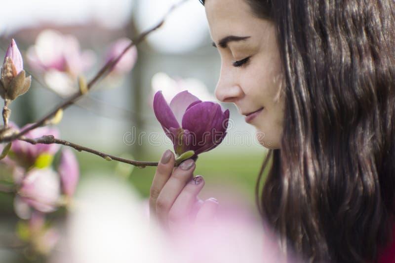 Mooi meisje die de bloemen ruiken Tot bloei komende magnolia in de parktuin royalty-vrije stock foto's