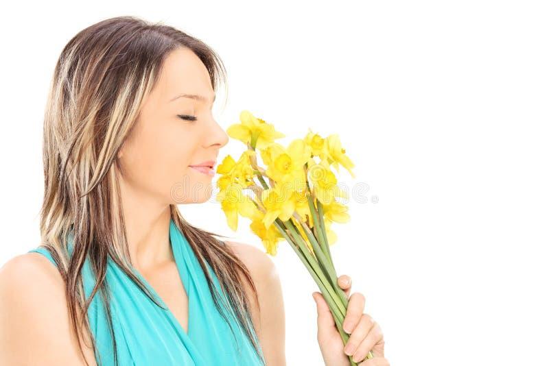 Mooi meisje die de geur van bloemen ruiken stock afbeeldingen