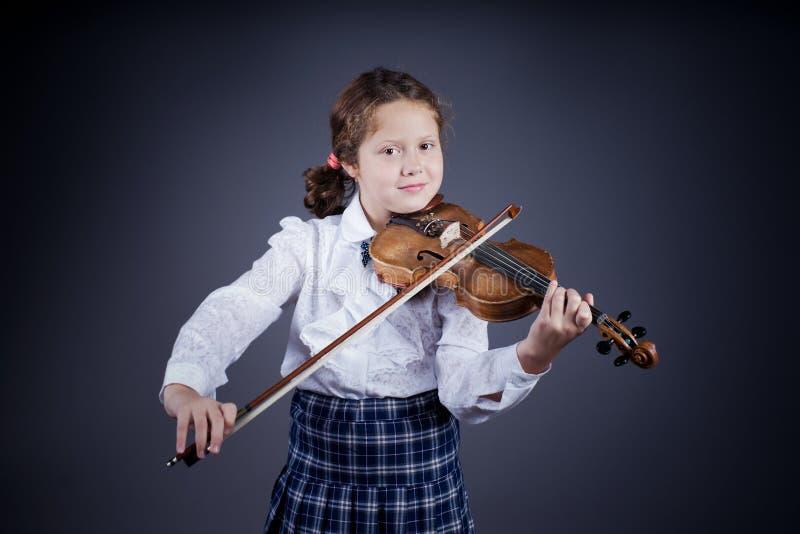 Mooi meisje die de oude viool op donkere achtergrond spelen stock foto's