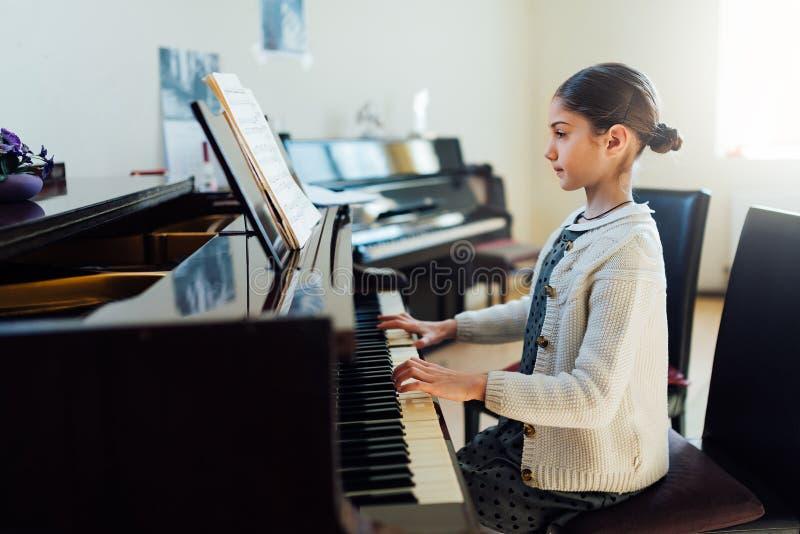 Mooi meisje die de piano spelen op School van Art. stock afbeelding
