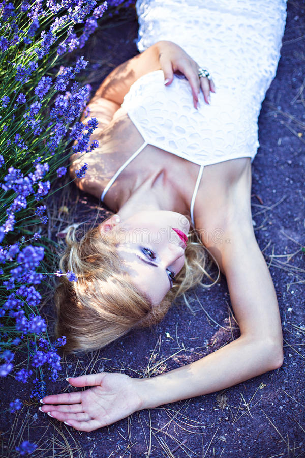 Mooi meisje die dichtbij bloeiende lavendel liggen stock afbeeldingen