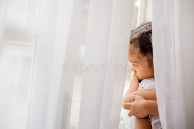 Mooi meisje die door het venster kijken stock afbeeldingen
