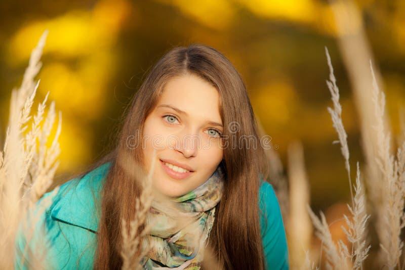 Mooi meisje die in droog gras liggen royalty-vrije stock afbeeldingen