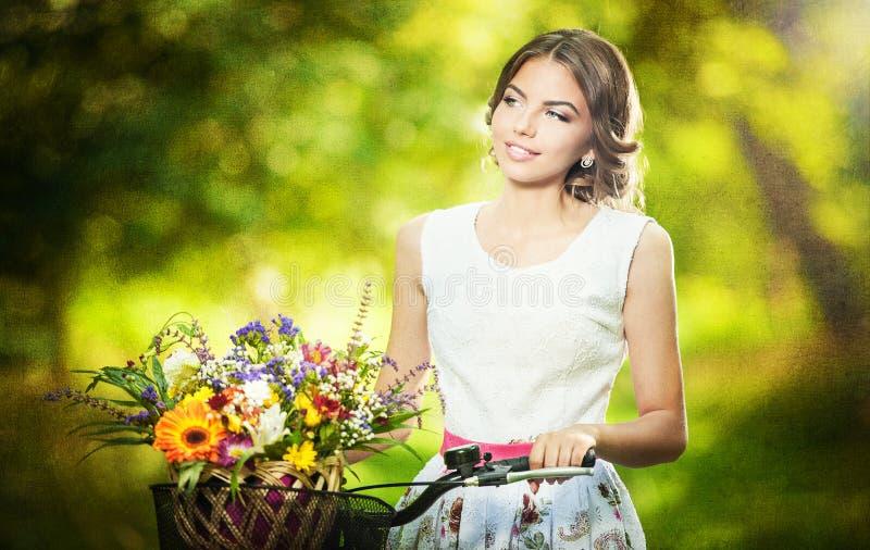 Mooi meisje die een aardige witte kleding dragen die pret in park met fiets hebben die een mooi mandhoogtepunt van bloemen dragen. stock afbeeldingen