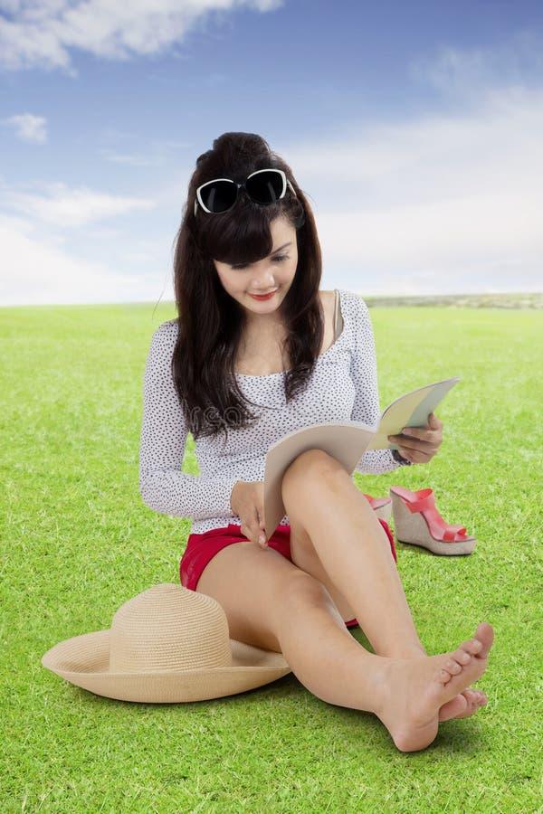 Mooi meisje die een boek in het park lezen stock fotografie
