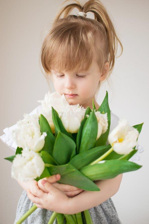 Mooi meisje die een boeket van bloemen houden royalty-vrije stock foto's