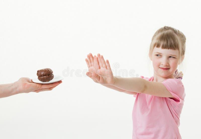 Mooi meisje die een chocoladecake regecting stock afbeelding