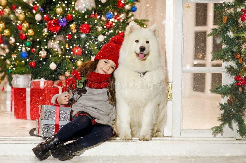 Mooi meisje die een grote witte hond in Kerstmisstree koesteren royalty-vrije stock fotografie